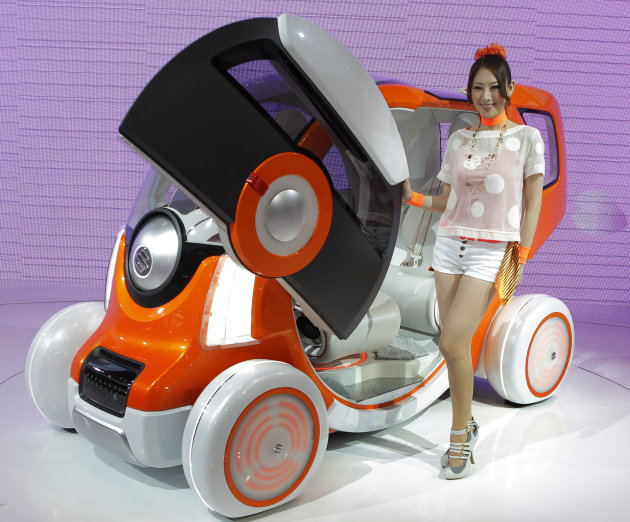 "A model poses by Suzuki Motor Corp.'s concept car ""Q-Concept"" during the press preview of Tokyo Motor Show in Tokyo Wednesday, Nov. 30, 2011. The Tokyo Motor Show opens to the public this weekend.(AP"