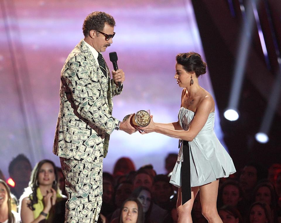 This April 14, 2013 photo shows actress Aubrey Plaza, right, as she tries to take away an award presented to Will Ferrell during the MTV Movie Awards in Culver City, Calif.  Plaza approached the stage as Ferrell made his acceptance speech after winning the Comedic Genius award. (Photo by Matt Sayles/Invision /AP)