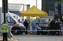 Police forensics officers investigate a crime scene where one man was killed in Woolwich