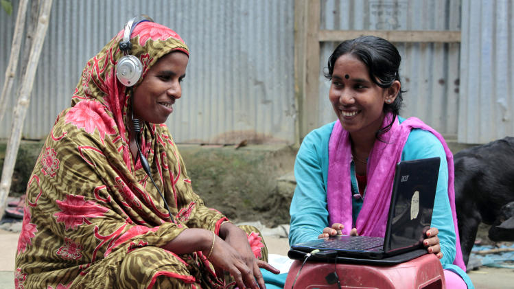 "In this Sept. 30, 2012, photo, Bangladeshi Info Lady Mehedi Akthar Misty, right, helps Amina Begum, 45, to talk with her husband with Skype at Jharabarsha, in a remote impoverished farming village in Gaibandha district, 120 miles (192 kilometers) north of capital Dhaka, Bangladesh. Begum had never seen a computer until a few years ago, but now she's on Skype regularly with her husband. A woman on a bicycle brings the Internet to her. Dozens of ""Info Ladies"" bike into remote Bangladeshi villages with laptops and Internet connections, helping tens of thousands of people - especially women - get everything from government services to chats with distant loved ones. (AP Photo/A.M. Ahad)"