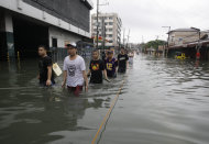 Filipinos wade along a flooded area in Quezon City, north of Manila, Philippines, Tuesday Aug. 7, 2012. Relentless rains submerged half of the sprawling Philippine capital, triggered a landslide that killed eight people and sent emergency crews scrambling Tuesday to rescue and evacuate tens of thousands of residents. (AP Photo/Aaron Favila)