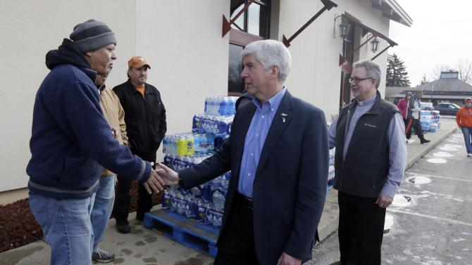 HOLD FOR STORY BY DAVID EGGERT- FILE- In a file photo from Feb. 5, 2016, Michigan Gov. Rick Snyder, center and Our Lady of Guadalupe Church Deacon Omar Odette, right, meet with volunteers helping to load vehicles with bottled water in Flint, Mich. Snyder's standing as one of the GOP's most accomplished governors has taken a beating in the lead-contaminated water emergency in Flint. Democrats, especially those running for president, are pointing to mistakes by Snyder's administration during the crisis as a vivid example of Republican-style cost-cutting run amok. (AP Photo/Carlos Osorio)