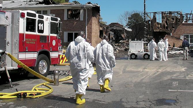 Investigators approach the damaged Mayfair Mews apartment complex in Virginia Beach, Va., on Saturday, April 7, 2012. The Navy and civilian authorities have just begun their investigation into the crash of the Navy F/A-18D fighter that hit the complex on Friday. (AP Photo/The Daily Press, Hugh Lessig)