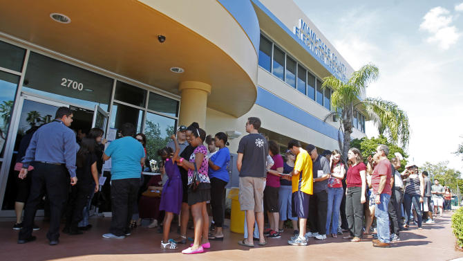 Voters stand in line to pick up their absentee ballots in Doral, Fla., Sunday, Nov. 4, 2012. Christina White, deputy supervisor with Miami-Dade County, said the county also decided to accept absentee ballots for four hours on Sunday at its main office. (AP Photo/Alan Diaz)