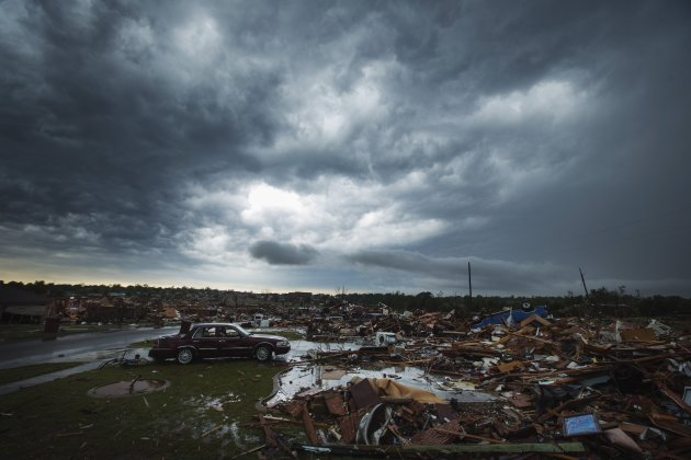 Clouds of a thunderstorm roll over neighborhoods heavily damaged in a tornado in Moore, Oklahoma