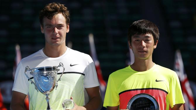 Safiullin of Russia and Hong of South Korea hold their trophies after their their junior boys' singles final match at the Australian Open 2015 tennis tournament in Melbourne