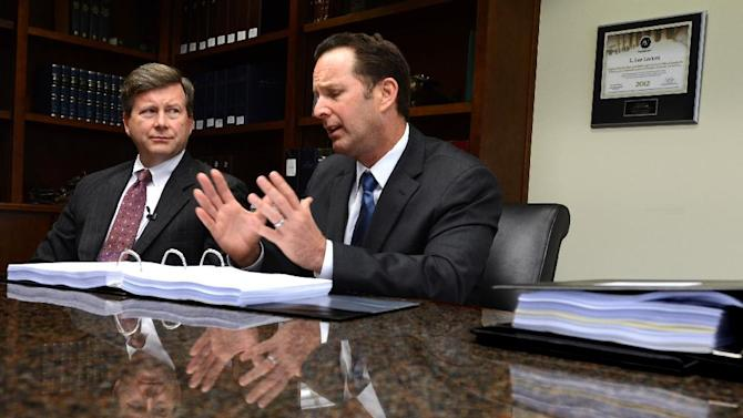 "Jacksonville, Fla.  attorney Kelly Mathis, left, listens as his attorney Mitch Stone explains their position at Stone's office in Ponte Vedra Beach, Fla., Wednesday, March 20, 2013. Mathis is accused by prosecutors as the ""mastermind"" of the Allied Veterans of the World internet gambling operation. (AP Photo/Rick Wilson)"