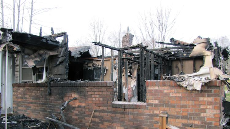 This photo shows the charred remains of  a home after a fire erupted, Saturday, March 9, 2013 in Gray, Ky. Fire erupted Saturday at a rural Kentucky home, killing two adults and five children inside, a coroner said. Knox County Coroner Mike Blevins said Saturday afternoon that the adult victims found inside the ranch-style home were a woman and her boyfriend. The woman was the mother of three of the children who died, while two other children were from another family, he said. (AP Photo/The Lexington Herald-Leader, Bill Estep)