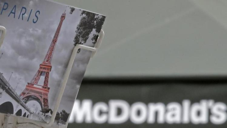 A postcard showing the Paris landmark the Eiffel Tower is seen in front of a McDonald's fast-food restaurant in Paris