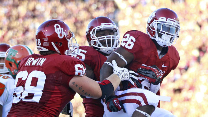 Oklahoma running back Damien Williams (26) celebrates with tight end Geneo Grissom (85) and offensive lineman Branson Irwin (69) following a touchdown against Florida A&M in the first quarter of an NCAA college football game in Norman, Okla., Saturday, Sept. 8, 2012. Oklahoma won 69-13. (AP Photo/Sue Ogrocki)