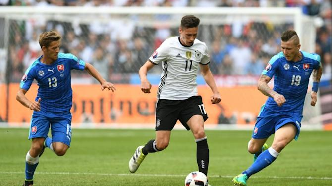 Germany's midfielder Julian Draxler (C) moves the ball down the pitch past Slovakian midfielders Patrik Hrosovsky and Juraj Kucka (R) during the Euro 2016 round of 16 football match at the Pierre-Mauroy stadium in Villeneuve-d'Ascq near Lille