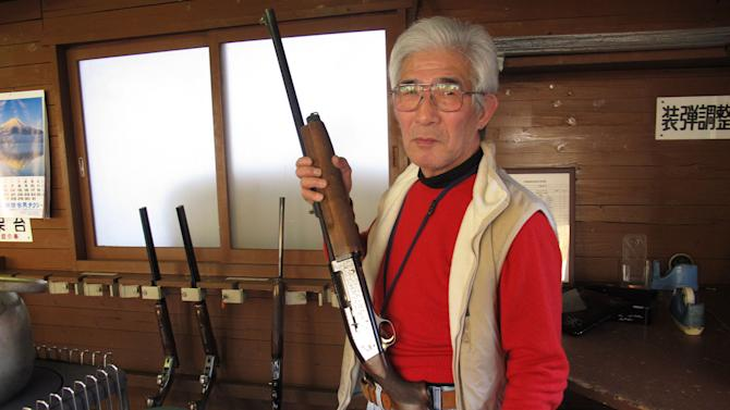 In this Friday, Jan. 18, 2013 photo, Japanese rifle enthusiast Yasuharu Watabe displays his gun at a shooting range in Ooi, near the foot of Mount Fuji, . Guns are few and far between in Japan because of strict regulations. But many gun-ownership supporters like Watabe say they don't want the kind of freedoms Americans have because they fear it would lead to more gun-related violence. (AP Photo/Eric Talmadge)
