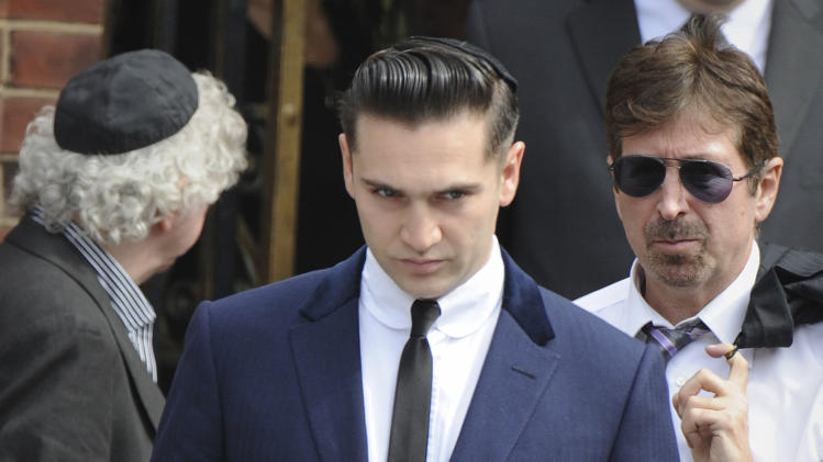 British film maker Reg Traviss, centre, a close friend, leaves Golders Green,Crematorium in London, Tuesday, July 26, 2011, after attending the funeral of singer Amy Winehouse.  The soul diva, who had battled alcohol and drug addiction, was found dead Saturday at her London home. She was 27. (AP Photo/Joel Ryan)