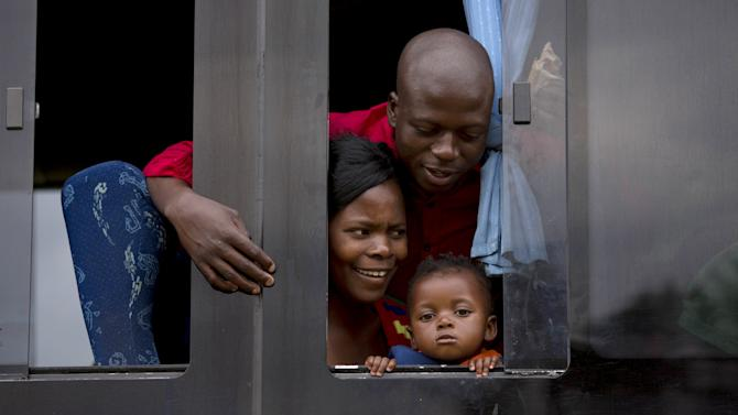 A family from Zimbabwe wait for a bus to depart for Harare, from a camp for those affected by anti-immigrant violence in Chatsworth, north of Durban