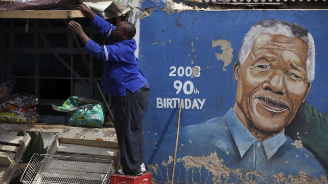 A man readies his shop near a mural showing former South African President Nelson Mandela in the Soweto area of Johannesburg, South Africa, Sunday, Dec. 9, 2012. South Africa's presidency says that Mandela, 94, was admitted to a hospital Saturday in the nation's capital for tests. (AP Photos/Jon Gambrell)