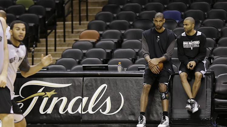San Antonio Spurs' Tim Duncan, left, and guard Tony Parker, right, of France, talk during a practice, Wednesday, June 12, 2013, in San Antonio. San Antonio will face the Miami Heat in game 4 of the NBA Finals basketball game Thursday. San Antonio leads the best-of-seven series 2-1. (AP Photo/Eric Gay)