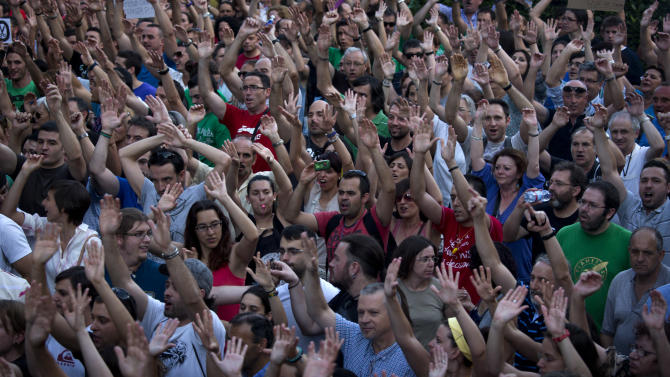 Demonstrators lift their hands and shout slogans as they protest against austerity measures announced by the Spanish government in Madrid, Spain, on Thursday July 19, 2012. Concerns over Spain's attempts to restore market confidence in its economy resurfaced Thursday after a bond auction went poorly and its borrowing costs edged higher — even as the country's Parliament passed the latest round of harsh austerity measures designed to cut its bloated deficit. (AP Photo/Emilio Morenatti)