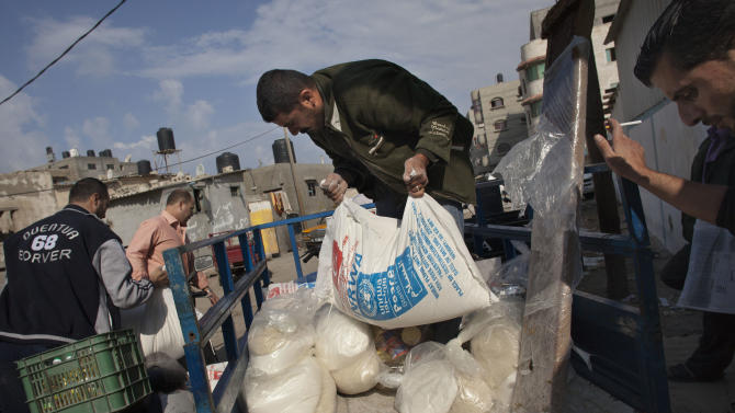 Palestinians collect bags of flour at a UN distribution center in Shati refugee camp, Gaza City, Monday, Nov. 19, 2012. Exchange of fire between Israel and Gaza militants continued for the sixth day on Monday. (AP Photo/Bernat Armangue)