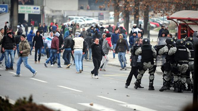 A group of ethnic Albanians throw stones at police during a violent protest in Skopje, Macedonia, on Saturday, March 2, 2013, as they show their support for newly named defence minister Talat Xhaferi, and as a contra-protest to Macedonian protests overnight Friday when scuffles broke out with police.  A series of scuffles erupted late on Friday and continued over night when a group of a few hundred Macedonians started protesting against the designation of the new defense minister Talat Xhaferi, an ethnic Albanian and former rebel commander.(AP Photo/Vangel Tanurovski)