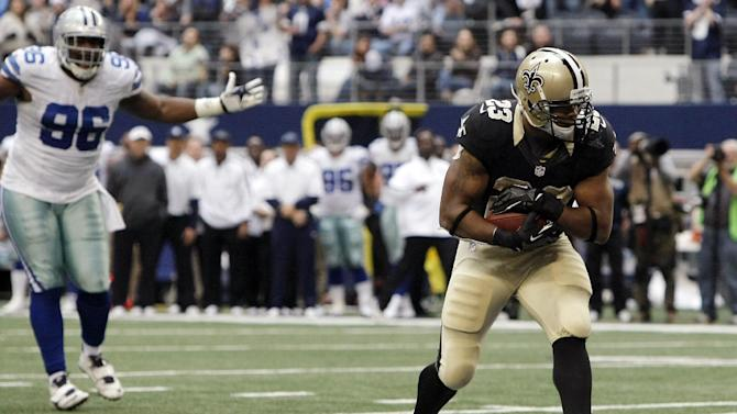 New Orleans Saints running back Pierre Thomas (23) scores a touchdown as Dallas Cowboys defensive end Marcus Spears (96) reacts during the second half of an NFL football game on Sunday, Dec. 23, 2012, in Arlington, Texas. (AP Photo/Brandon Wade)