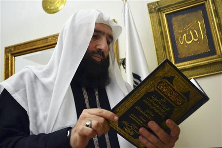 Islamist preacher Omar Bakri takes a look at a religious book during an interview with Reuters at his home in Tripoli, northern Lebanon
