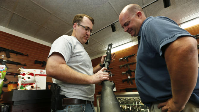 Black Weapons Armory store owner Tommy Rompel, left, shows former mayoral candidate Shaun McClusky, a shotgun at the Tucson, Ariz. store on Thursday, March 28, 2013. The weapon is similar to those to be given away as part of a privately funded program he is launching to provide residents in crime-prone areas with free shotguns so they can defend themselves against criminals. (AP Photo/Ross D. Franklin)