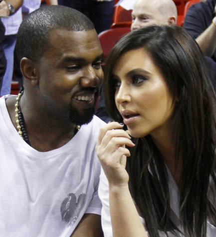 FILE - In this Dec. 6, 2012 file photo singer Kanye West, left, talks to his girlfriend Kim Kardashian before an NBA basketball game between the Miami Heat and the New York Knicks in Miami. Authorities say an airline employee is being investigated for allowing West and Kardashian to bypass a security checkpoint at New York&#39;s Kennedy Airport. (AP Photo/Alan Diaz, File)
