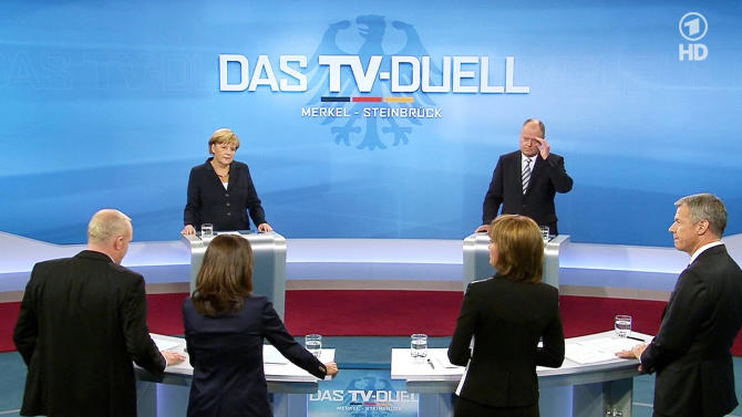 Photo provided by German broadcaster WDR shows German Chancellor Angela Merkel, background left, of the Christian Democrats and her Social Democratic challenger Peer Steinbrueck, background right, with journalists, from left, Stefan Raab, Anne Will, Maybrit Illner und Peter Kloeppel during the only live televised debate ahead of the national elections in Berlin, Sunday, Sept. 1, 2013. Germany is facing general elections on Sept. 22, 2013. (AP Photo/WDR)