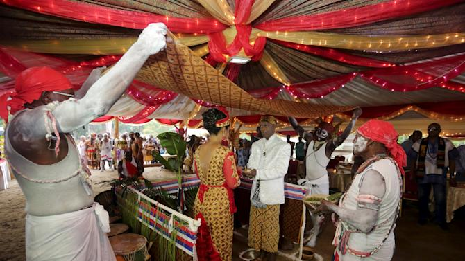 Winti spiritual leader Ramon Mac-Nack and his bride Melissa Karwafodi stand under a ceremonial cloth as they are married in the first Winti marriage ever to be held in public in district Para