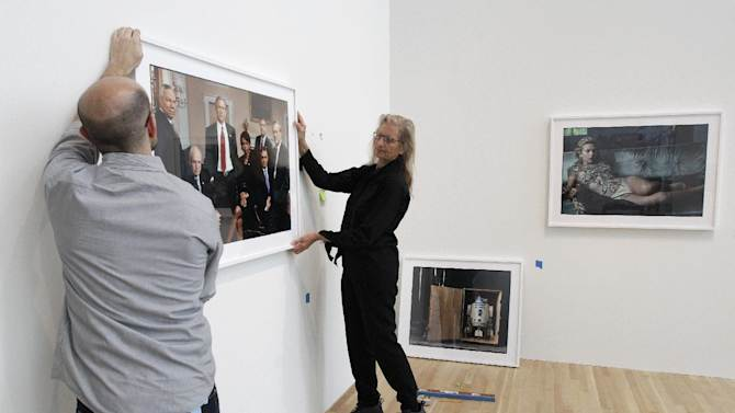 """Annie Leibovitz, right, helps Zak Kelley, of Columbus, hang one of her photographic prints before the opening of her exhibition at the Wexner Center for the Arts Friday, Sept. 21, 2012, in Columbus, Ohio. Leibovitz's exhibition features work from her """"Master Set,"""" an authoritative edition of 156 images. (AP Photo/Jay LaPrete)"""