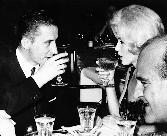 FILE - In this February 26, 1962 file photo, Marilyn Monroe and Jean Pierre Piquet, left, manager of Continental Hilton Hotel, are seen lifting their champagne glasses at a reception offered to the visiting star, in Mexico City. In late 2012, the FBI has released a new version of files it kept on Monroe that reveal the names of some of her acquaintances who had drawn concern from government officials and members of her entourage over their suspected ties to communism. (AP Photo, File)