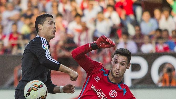 Real Madrid's Cristiano Ronaldo, left, tries to score against Sevilla's Sergio Rico, right, during a Spanish La Liga soccer match between Sevilla and Real Madrid at the Ramon Sanchez Pizjuan Stadium in Sevilla, Spain Saturday, May 2, 2015. (AP Photo/Andres Kudacki)