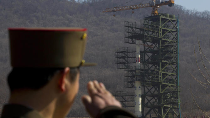 FILE - In this April 8, 2012, file photo, a North Korean soldier salutes in front of the country's Unha-3 rocket, slated for liftoff between April 12-16, at Sohae Satellite Station in Tongchang-ri, North Korea.  North Korea may postpone the controversial launch of a long-range rocket that had been slated for liftoff as early as Monday, Dec. 10, 2012, North Korean state media said Sunday, Dec. 9, 2012. North Korea announced earlier this month that it would launch a three-stage rocket mounted with a satellite from its Sohae station southeast of Sinuiju sometime between Dec. 10 and Dec. 22.  (AP Photo/David Guttenfelder, File)