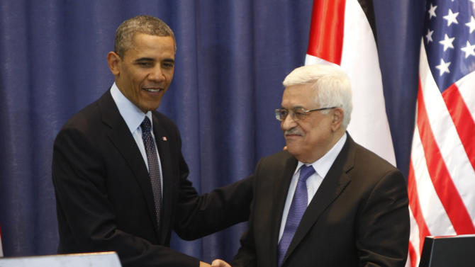 US President Barack Obama, left, shakes hands with Palestinian President Mahmoud Abbas during a joint press conference in the West Bank city of Ramallah, Thursday, March. 21, 2013. Obama on Thursday urged Israelis and Palestinians to get back to peace talks but offered no new ideas on how they might do so, essentially abandoning his previous support of the Palestinian demand for Israel to halt settlement activity before negotiations resume. (AP Photo/Majdi Mohammed)