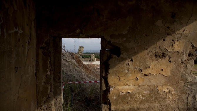 A military Iron Dome defense missile system, designed to intercept and destroy incoming short-range rockets and artillery shells from Gaza, is seen through an abandoned house near Tel Aviv Sunday, Nov. 18, 2012. (AP Photo/Oded Balilty)