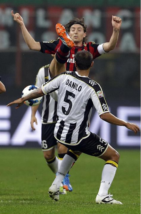 AC Milan's Riccardo Montolivo, top, is challenged by Udinese defender Danilo during a Serie A soccer match between AC Milan and Udinese, at the San Siro stadium in Milan, Italy, Saturday, Oct. 19, 201