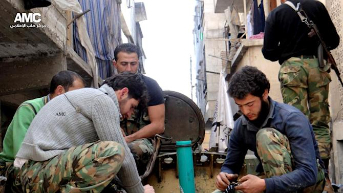 FILE - This Thursday, April 25, 2013 file photo citizen journalism image provided by Aleppo Media Center AMC which has been authenticated based on its contents and other AP reporting, shows members of the free Syrian Army preparing their weapons, in the neighborhood of al-Amerieh in Aleppo, Syria. Rebels are pressing for a decision from the West on arming their forces to even their odds now that Lebanon's Hezbollah guerrillas are fighting alongside the regime. They are stepping up outreach to the West, warning that inaction will let al-Qaida-linked militants take the forefront in the rebellion or hand victory to Iran and Hezbollah. (AP Photo/Aleppo Media Center AMC, File)