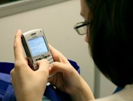 A woman texts on her mobile phone. The amount of time that Britons spend talking on their mobile phones has dropped for the first time -- by one billion minutes, a new Ofcom report revealed on Wednesday