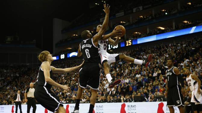 Anderson of the Brooklyn Nets tries to block Teague of the Atlanta Hawks during their NBA basketball game at the O2 in London