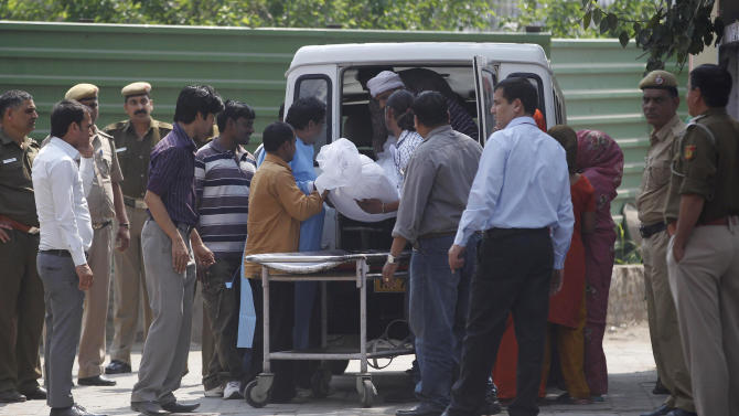 Unidentified relatives of Ram Singh, one of the men on trial for his alleged involvement in the gang rape and fatal beating of a woman aboard a New Delhi bus , carry Singh's body in to a waiting hearse outside a mortuary in New Delhi, India, Tuesday, March 12, 2013. The body of the man who died in a New Delhi jail while in the midst of a high-profile rape trial was released to his family Tuesday after a post-mortem exam aimed at determining whether he committed suicide or was killed. (AP Photo/ Mustafa Quraishi)