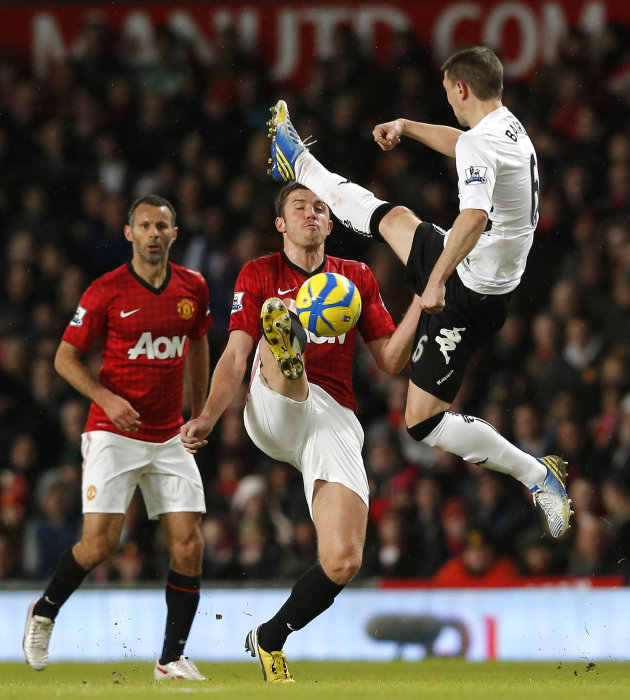 Manchester United's Carrick is challenged by Fulham's Baird during their FA Cup fourth round soccer match at Old Trafford in Manchester
