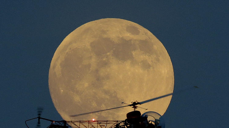 The moon is seen in its waxing gibbous stage as it rises behind the helicopter from the original Batman television show, which people can ride at the New Jersey State Fair, Saturday, June 22, 2013, in East Rutherford, N.J. The moon, which will reach its full stage on Sunday, is expected to be 13.5 percent closer to earth during a phenomenon known as supermoon. (AP Photo/Julio Cortez)