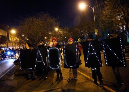 Demonstrators hold signs bearing the name of Laquan McDonald during protests in Chicago