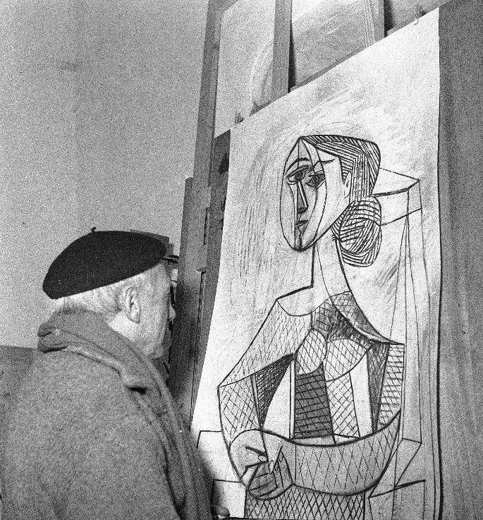 "FILE - In this April 8, 1953 file photo, artist Pablo Picasso looks at a recent painting, ""Portrait of a Woman,"" in his studio in Vallauris, French Riviera. (AP Photo)"