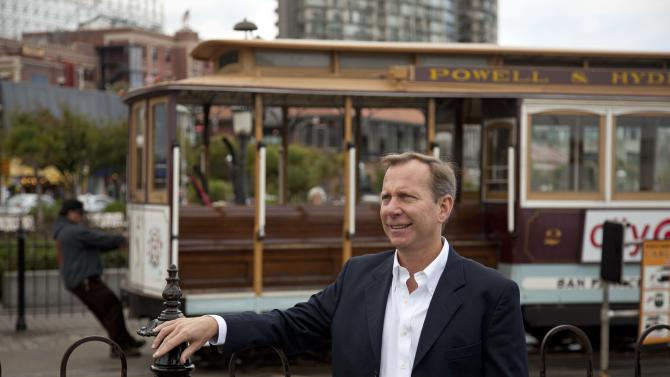 In this photo taken Thursday, Oct. 25, 2012, Michael Ellis, the new worldwide director of Michelin Guide, poses by the Hyde Street cable car turnaround and Ghirardelli Square near Fisherman's Wharf in San Francisco. Ellis took over this year as head of the guides, becoming the first U.S.-born (and first non-Frenchman) to head the Michelin Guide. (AP Photo/Eric Risberg)