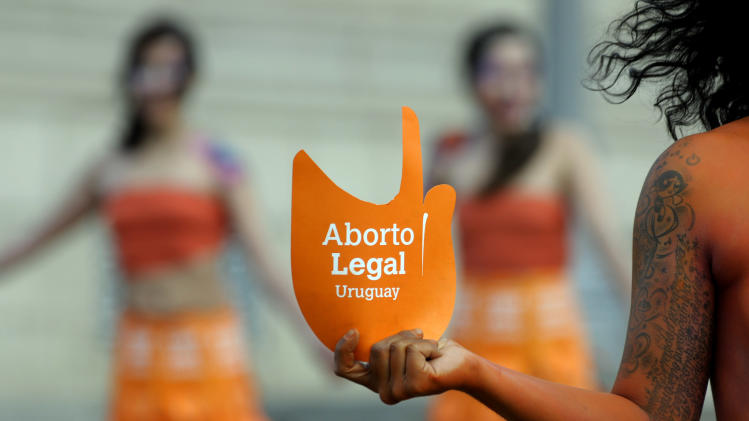 "Pro abortion activists demonstrate in front of the Uruguayan congress in Montevideo, Uruguay, Tuesday, Sept. 25, 2012. Uruguay's congress appeared ready on Tuesday to legalize abortion, a groundbreaking move in Latin America, where no country save Cuba has made abortions accessible to all women during the first trimester of pregnancy. The sign reads in Spanish ""legal abortion.""  (AP Photo/Matilde Campodonico)"