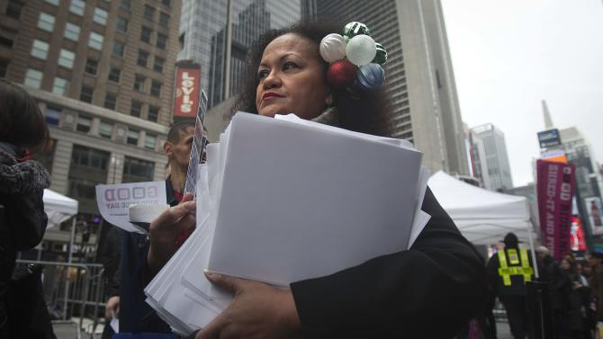 "Actress Boquita Almonte waits in line with an armful of papers she wants to shred on ""Good Riddance Day"" in Times Square in New York"