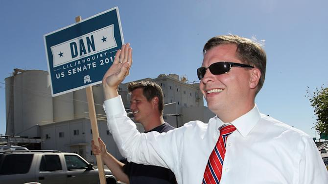 Former Utah state senator, Dan Liljenquist, right, waves to motorists during last minute campaigning in a primary election against incumbent senator Orrin Hatch, R-Utah, Tuesday, June 26, 2012, in Salt Lake City. (AP Photo/Colin E. Braley)