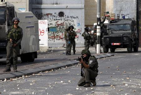 Israeli border policeman aims his weapon at Palestinians during clashes in the occupied West Bank city of Bethlehem