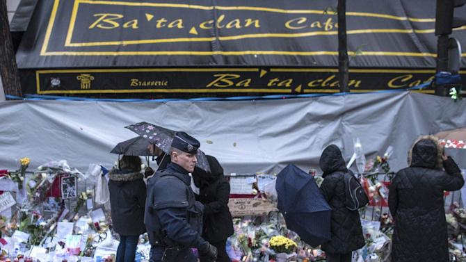 FILE - In this Nov. 25, 2015 file photo, a policeman walks as people pay respects to victims of the Paris attacks in front of the Bataclan concert hall, in Paris. The owners of the Paris concert hall where 89 people were massacred by Islamic extremists say Wednesday Feb.10, 2016 they are aiming to host music shows again before the end of the year. (AP Photo/Kamil Zihnioglu, File)